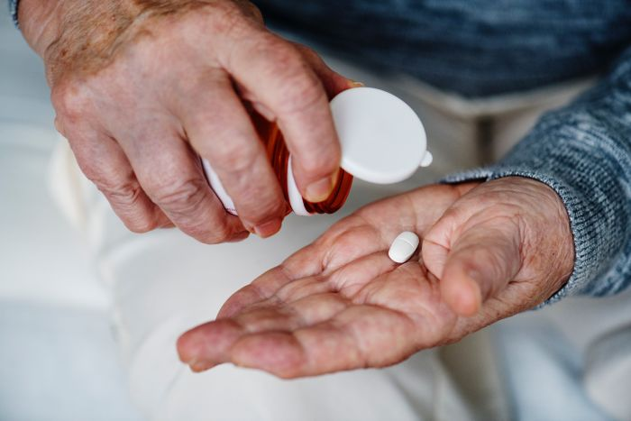 A person tipping a pill out of a bottle