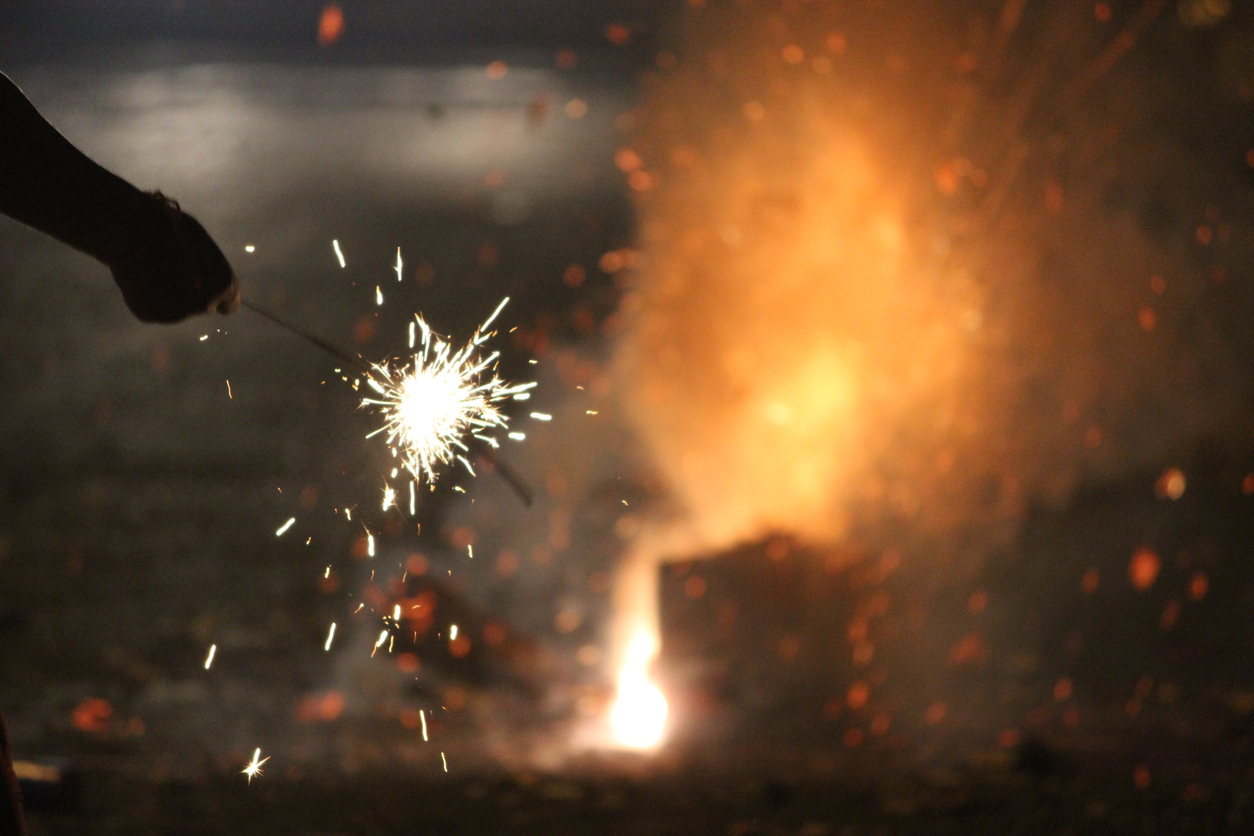 Person holding a lit firework during the Diwali festival of lights