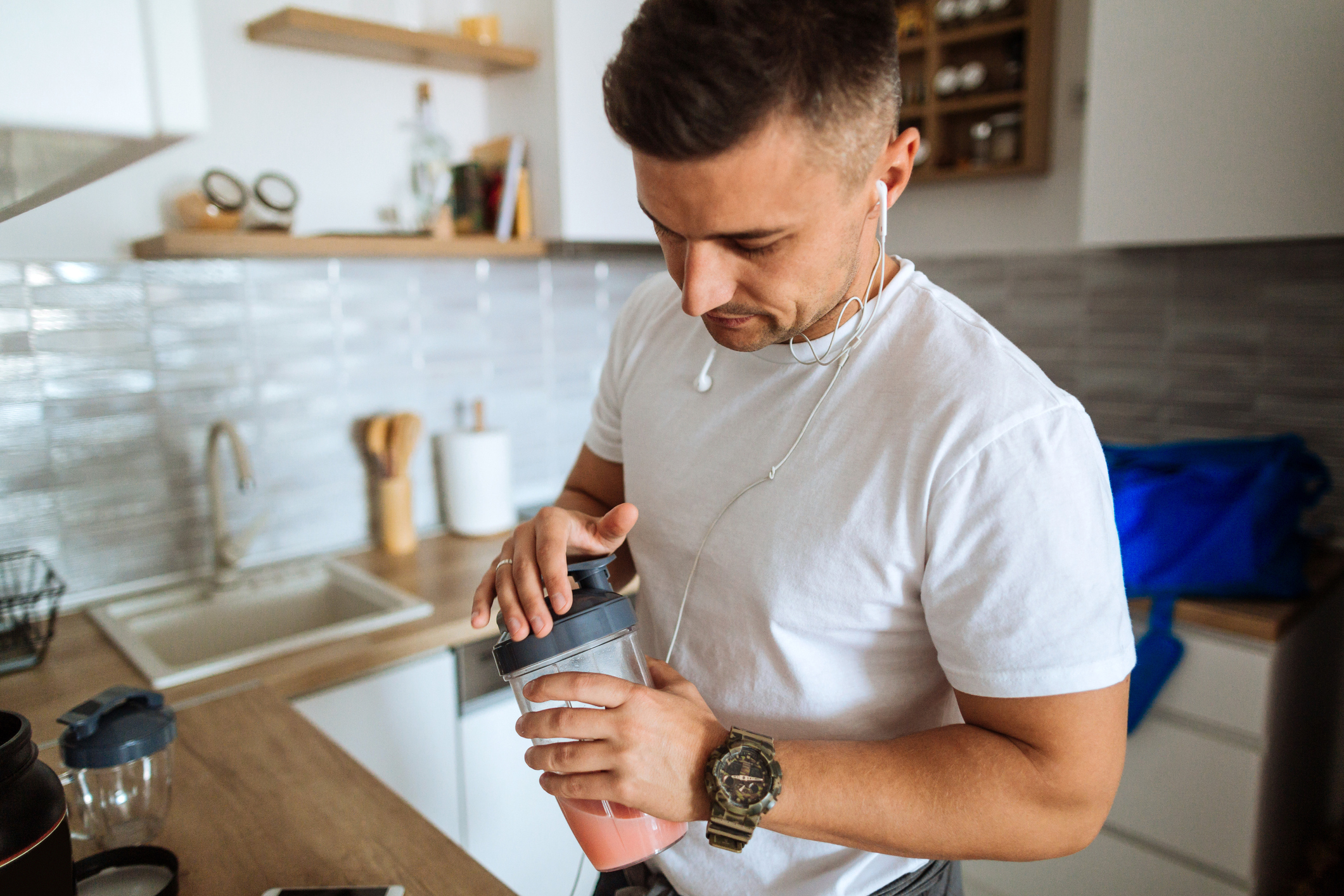 man in his kitchen, putting the lid on a protein shake