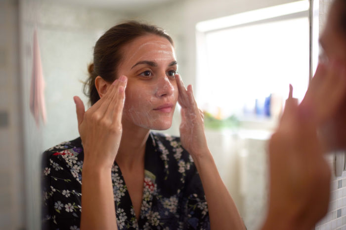 Woman with acne cleaning her face