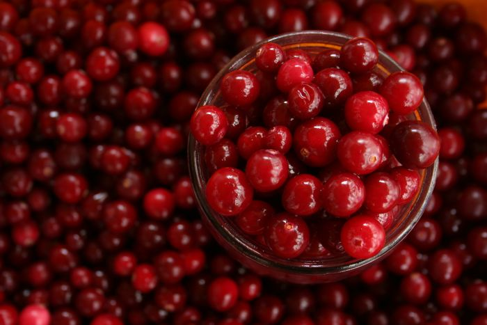 Photograph of cranberries in a pile and a glass