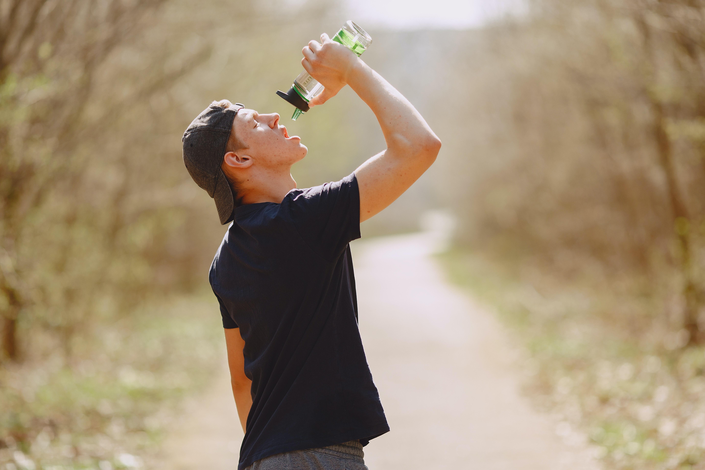व्यायाम करता हुआ व्यक्ति पानी पीते हुए