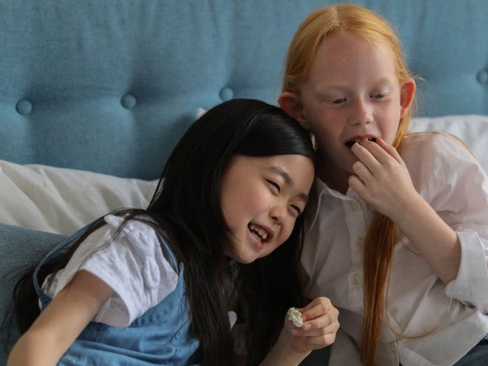 Friends eating popcorn on bed at home