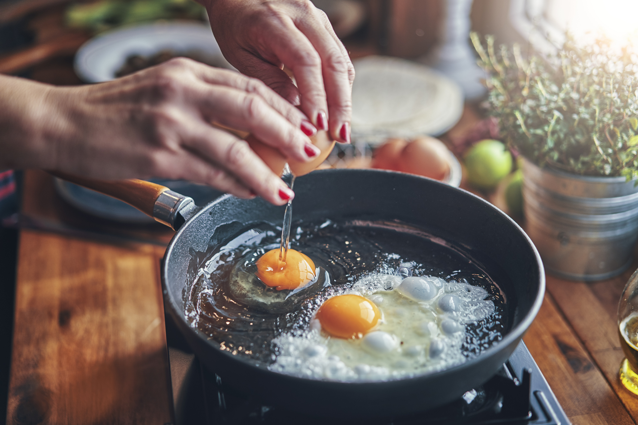 close up of someone frying an egg in a pan