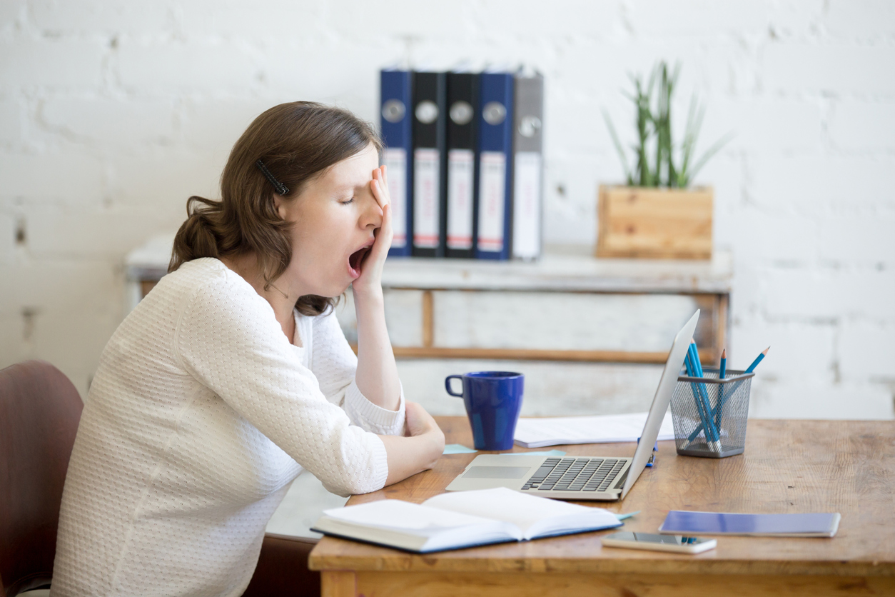 Young woman looking tired and yawning at her desk