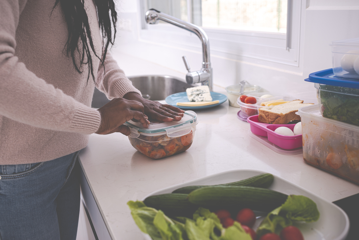 Woman packing leftovers into a plastic container in a kitchen