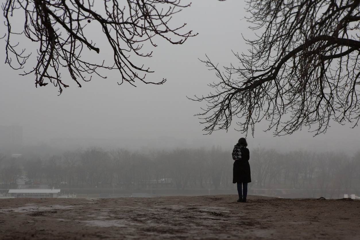 Girl standing alone in the park on a gloomy day (credit - BenAkiba)