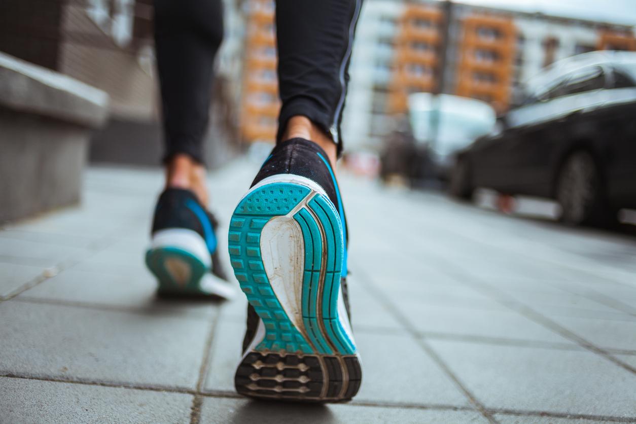 एक महिला प्रशिक्षक फुटपाथ पर चलते हुए