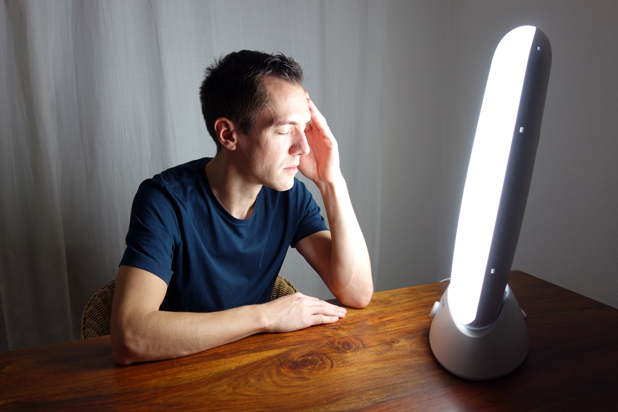 Man sitting at a table having light therapy treatment (credit - Rocky89)