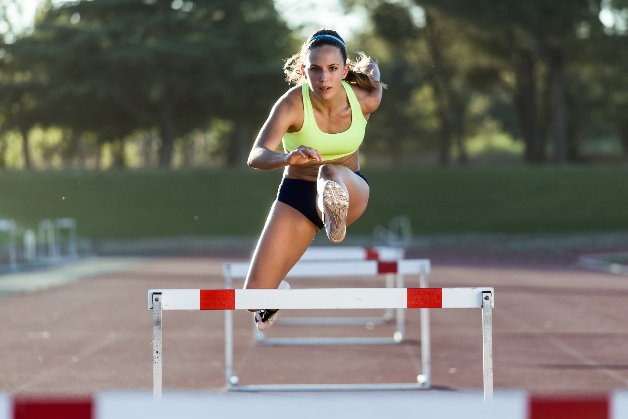 Female athlete jumping over hurdles