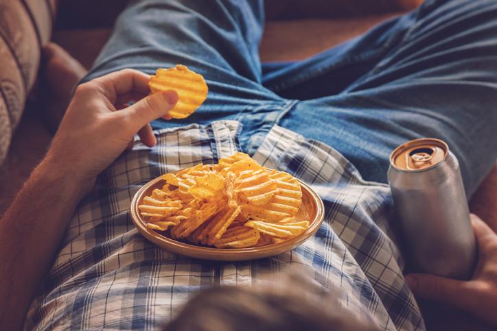 सोफे पर लेटा हुआ आदमी, बियर पीते हुए, चिप्स खाते हुए और टीवी देखते हुए  .