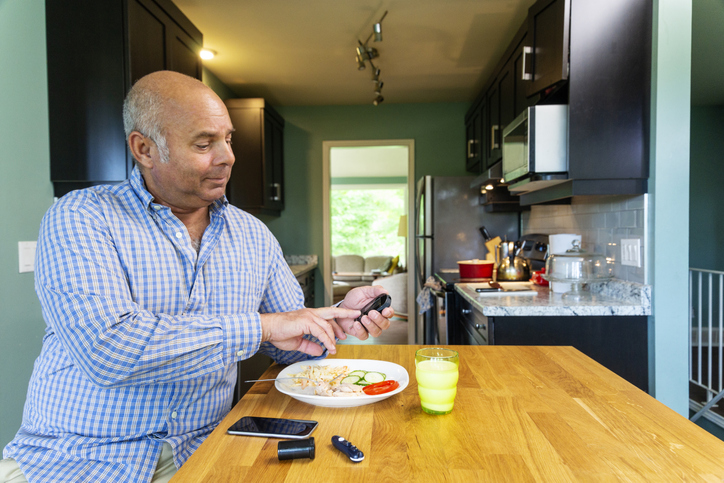 A diabetic patient in his kitchen testing his blood sugar prior to eating a healthy meal.