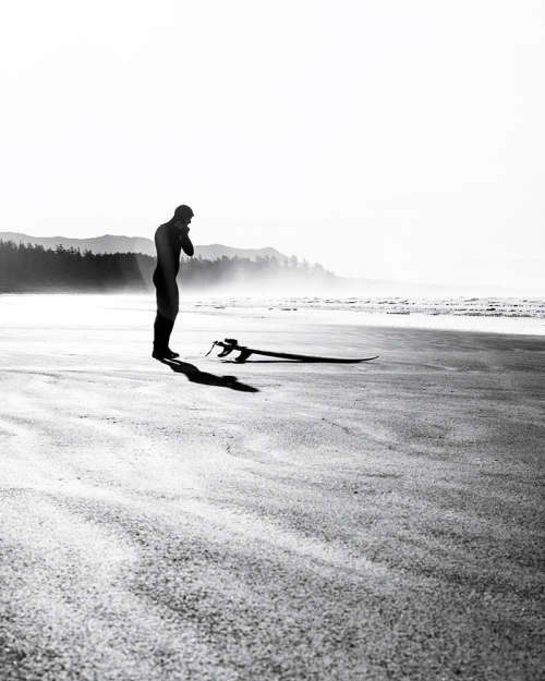A black and white photo of a surfer adjusting his hooded wetsuit on Long Beach