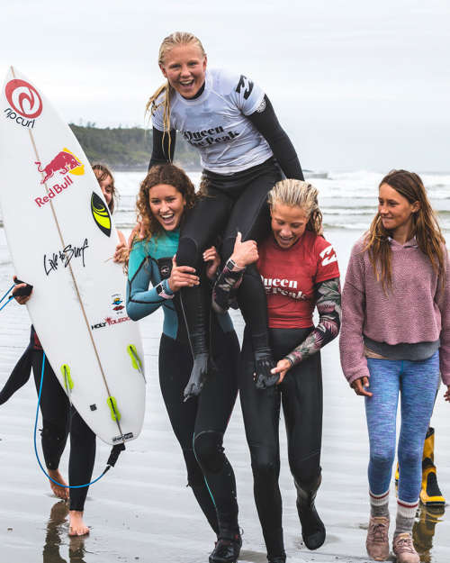 A group of five female surfing friends have fun on a beach in Tofino