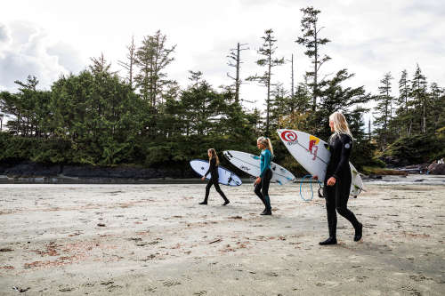 The two Olin sisters and their friend trek across the Cox Bay beach with their surfboards