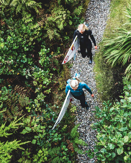 Sanoa and Mathea Olin head down a forest path with their surfboards