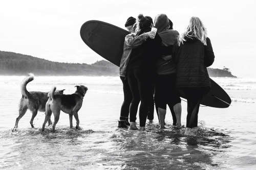A black and white photo of a surfer getting hugged by supporters beside two dogs on a Tofino beach