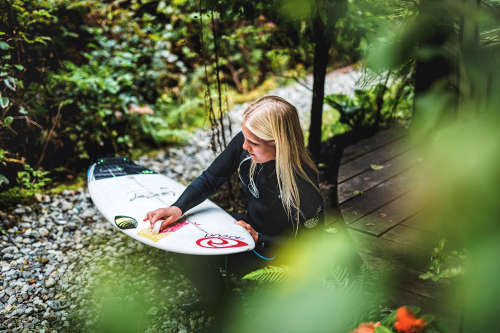 Mathea Olin waxes her shortboard amongst the Tofino foliage