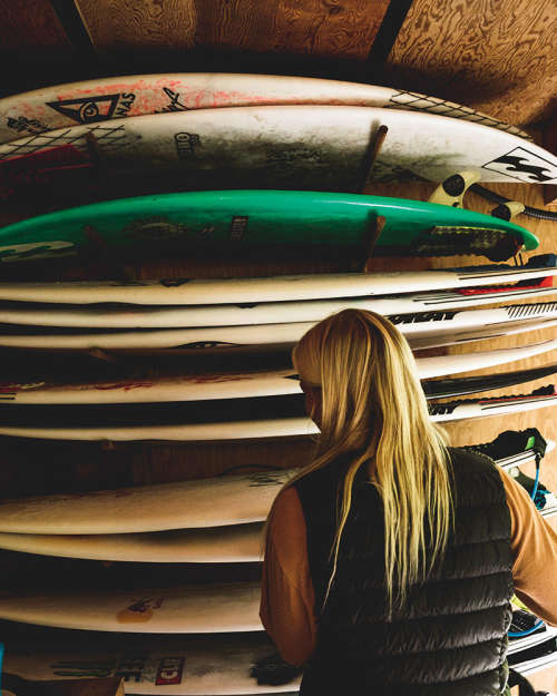 Mathea Olin looks at her wall of surf boards