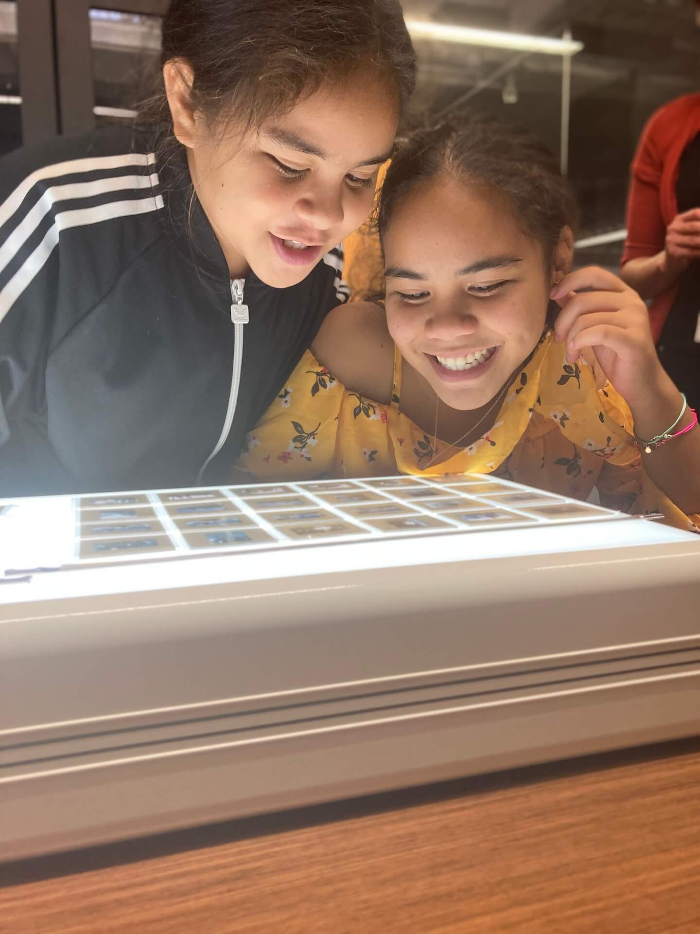 Two girls smiling looking at slides on lighting table.
