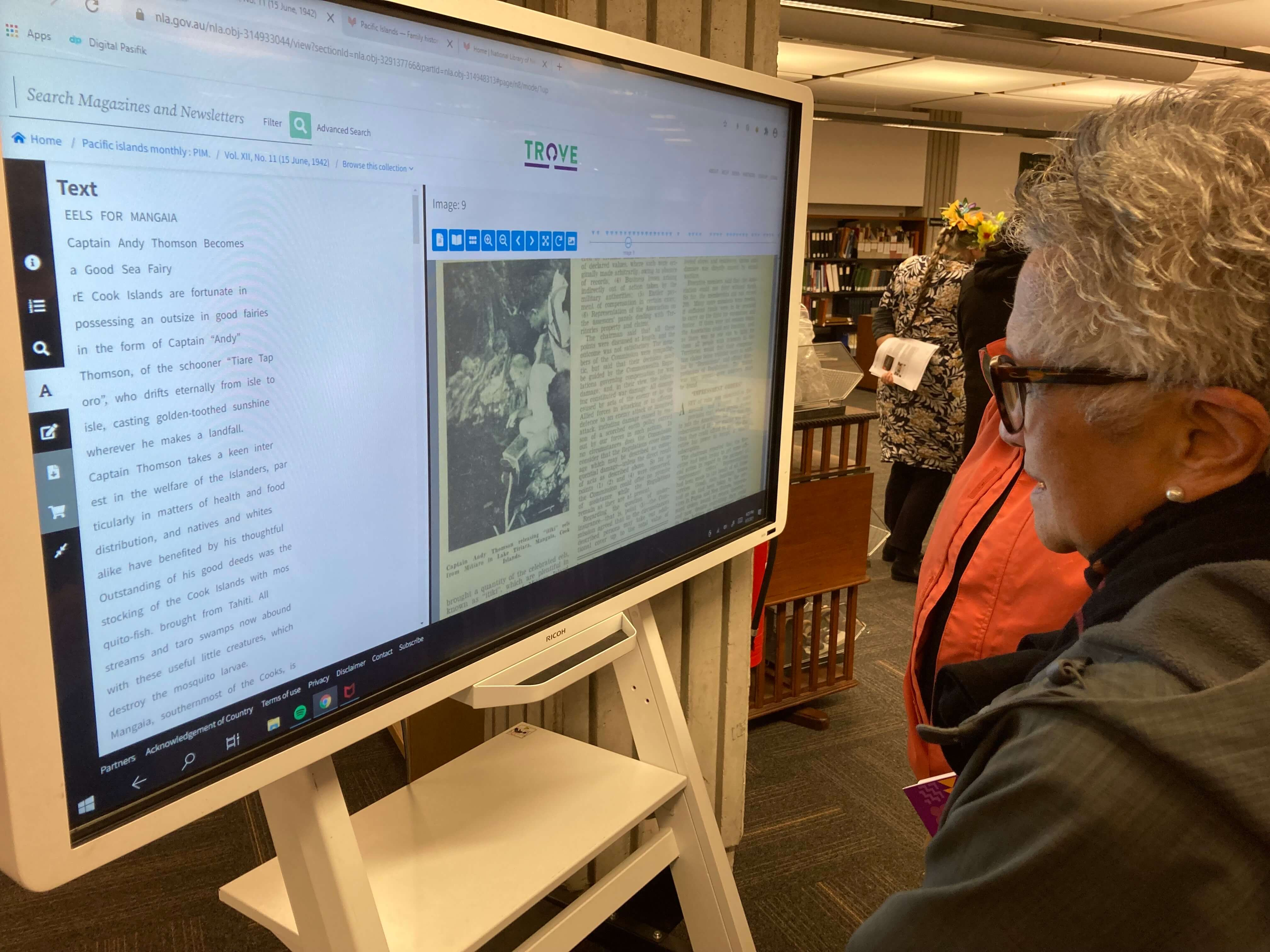 Grey haired woman looking at TV screen reading text.