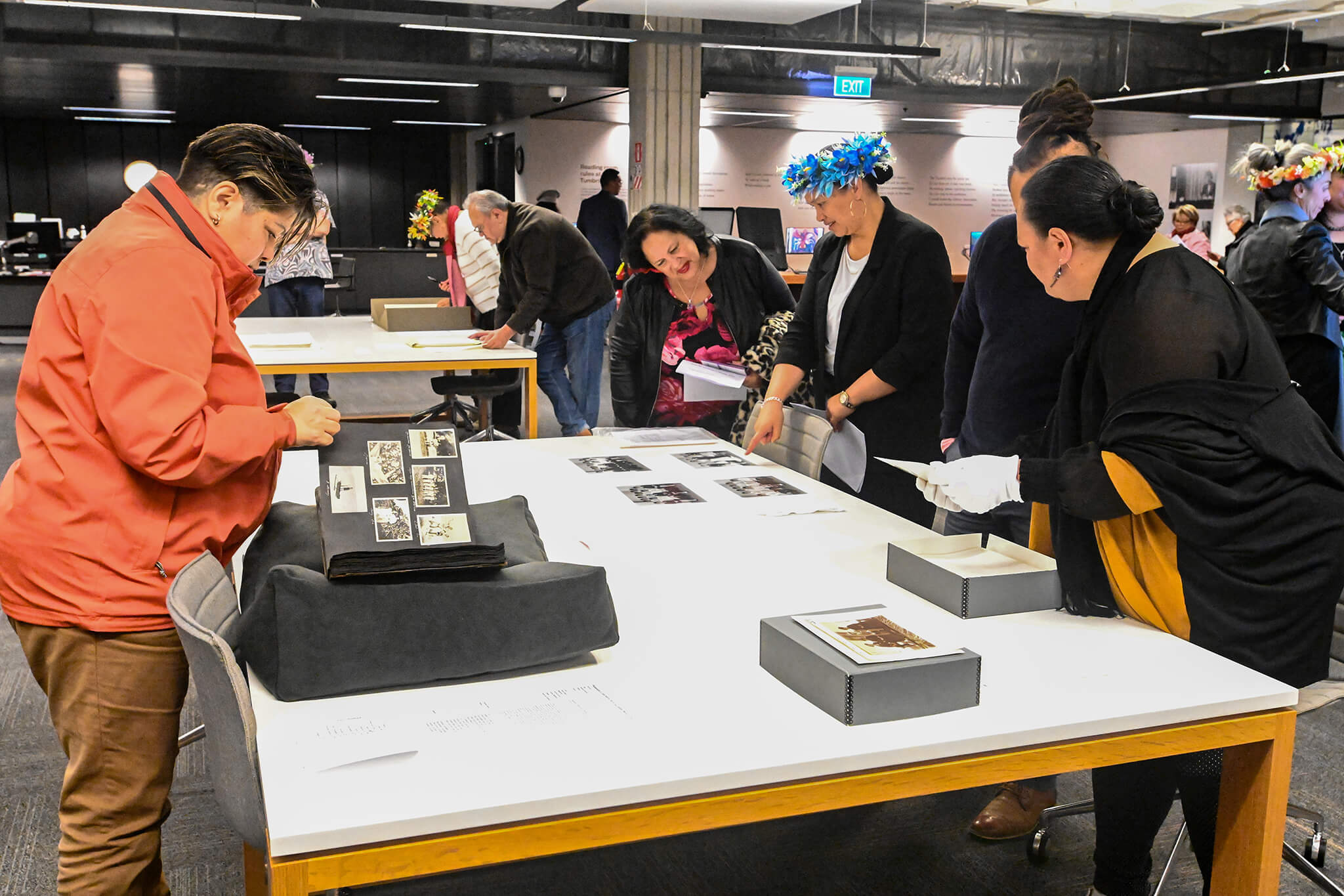 Women gathered around a table looking at photographs