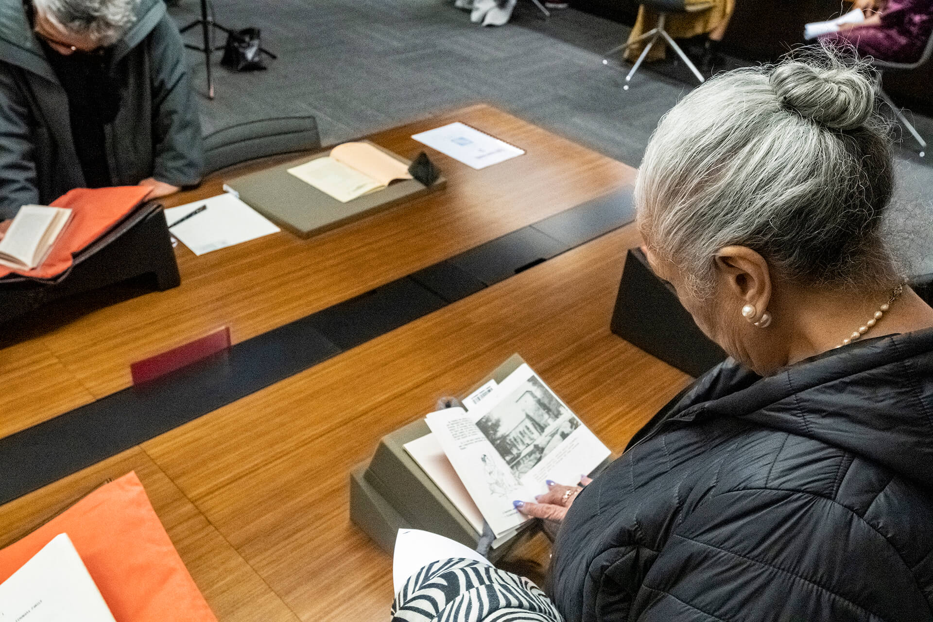 Grey haired woman looking at book on a table