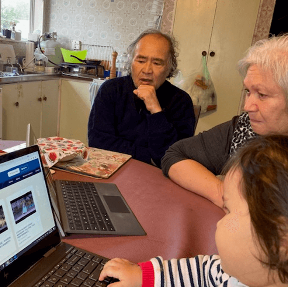A older male, older female and child looking at laptop screens.