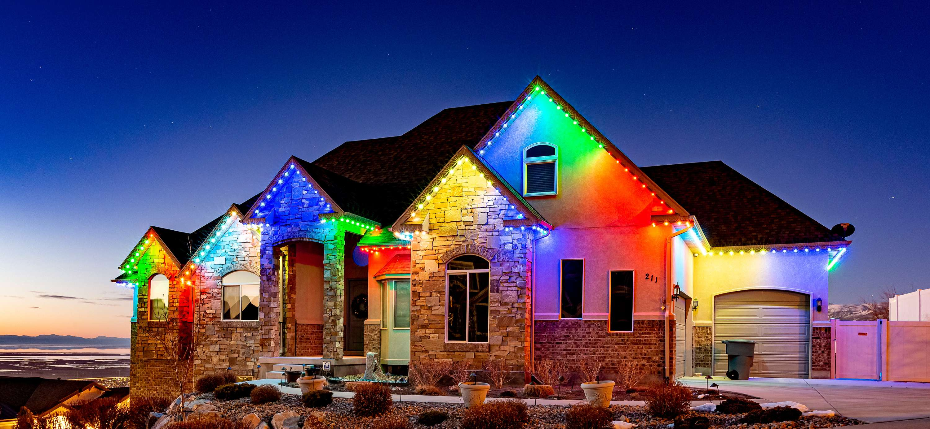 a large home with trimlight red and green lights along the trim