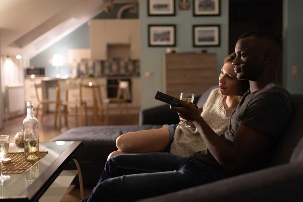 пара смотрит фильм на диване