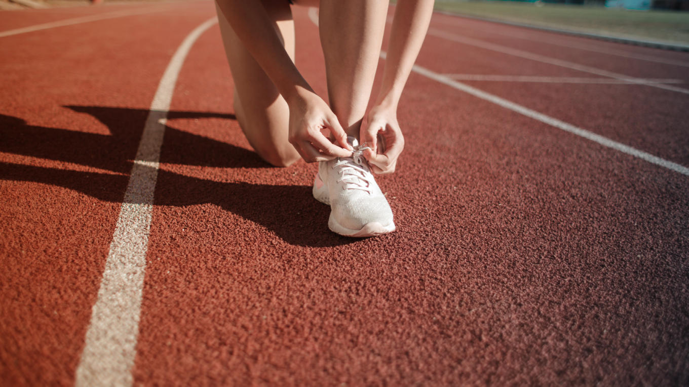 A runner ties their shoe before a sprint.