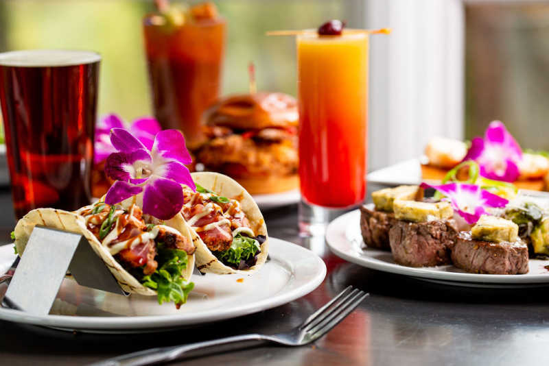 Flower-topped filet medallions and ahi tuna tacos are accompanied by a pint of craft beer and a vibrantly colored cocktail.