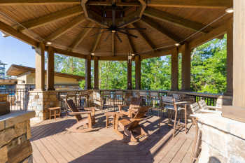 A large gazebo made of wood and stone overlooks the pool, trees, and Lake Hartwell, while Adirondack rocking chairs positioned below a large ceiling fan offer invite guests to take a load off.