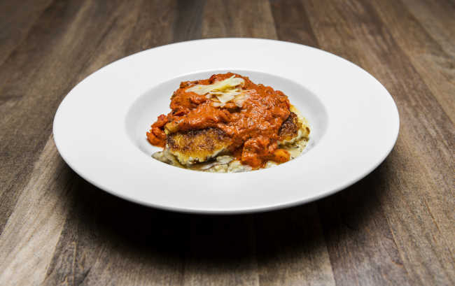 Traditions on the Lake's potato-crusted grouper is topped with red Creole gravy and served on a bed of andouille mushroom risotto.