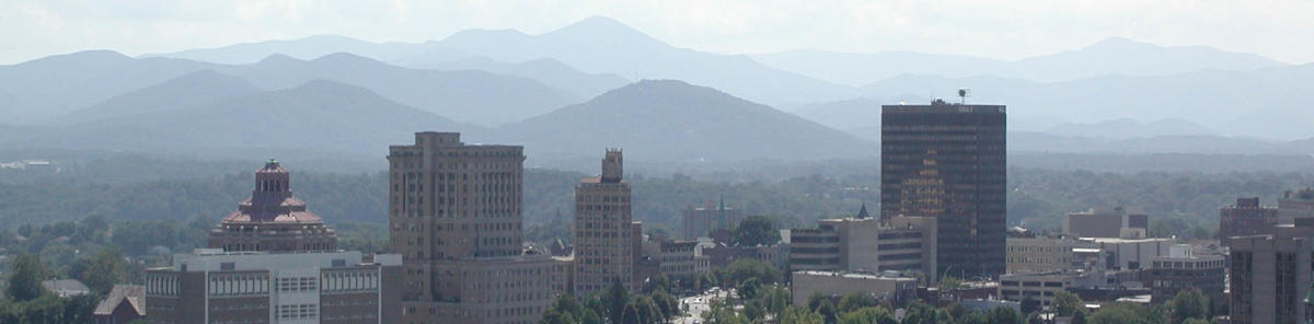Downtown Asheville's classic Art Deco buildings rise against a background featuring Mt. Pisgah and its neighboring Blue Ridge peaks.