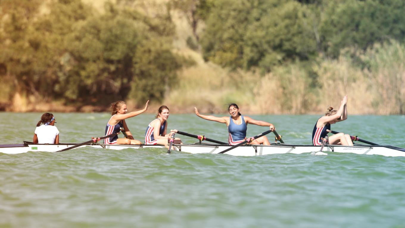 A women's crew team celebrate in their boat after a race.