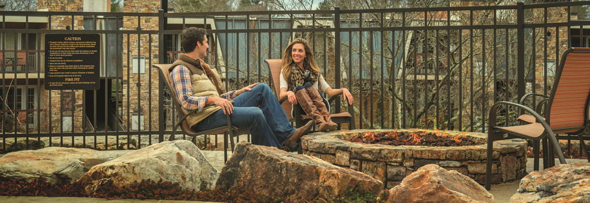 A young couple, dressed for autumn weather, sit beside the stone fire pit at The Residences at Biltmore.