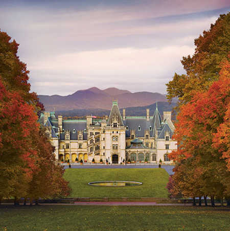 The main entrance of Biltmore is framed between autumn-colored trees, while the high peaks of the Smoky Mountains crest in the distance.