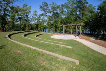 Three grassy tiers of amphitheater seating face a round, trellis-covered concrete pad, while beyond a narrow stand of trees, Lake Hartwell reflects a clear, blue sky.