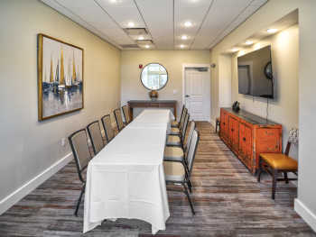 The private dining room at Traditions on the Lake, including a long banquet table with seating for 10 to 12 and a large, wall-mounted LED TV.