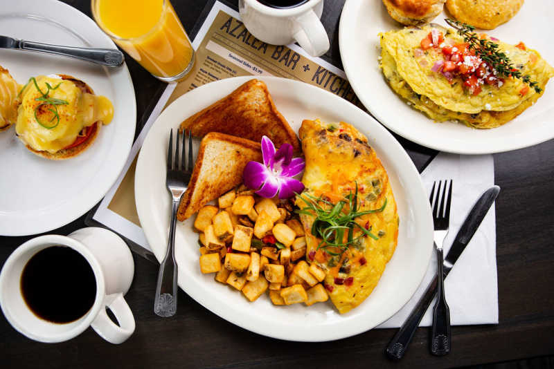 A spread of items from Azalea Kitchen's breakfast menu, including an omelette with home fries and toast, fresh-baked biscuits, eggs Benedict, and a mug of hot coffee.