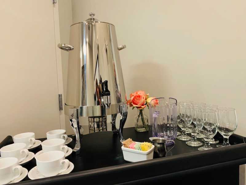 An assortment of glass stemware and espresso cups share a bar top with a stainless steel drink cooler and two pink roses.