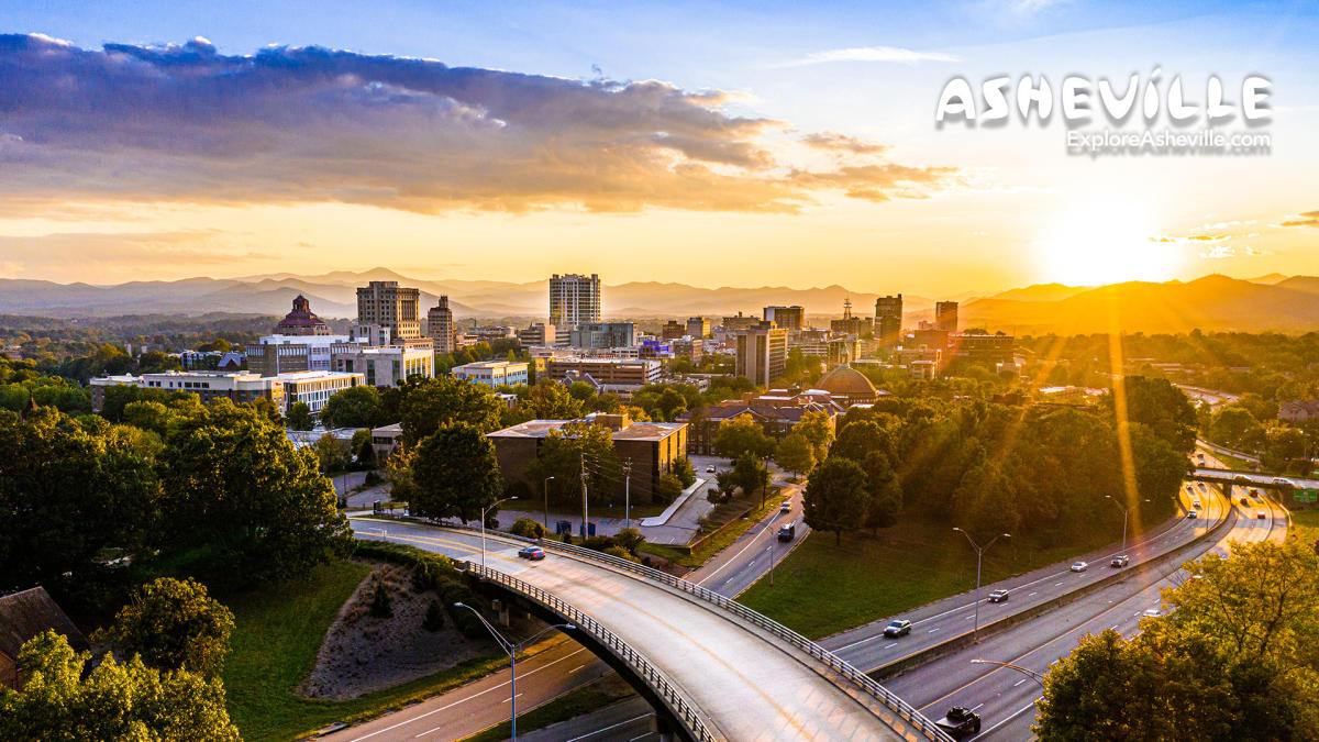A bird's eye view of downtown Asheville as the sun sets behind the mountains.