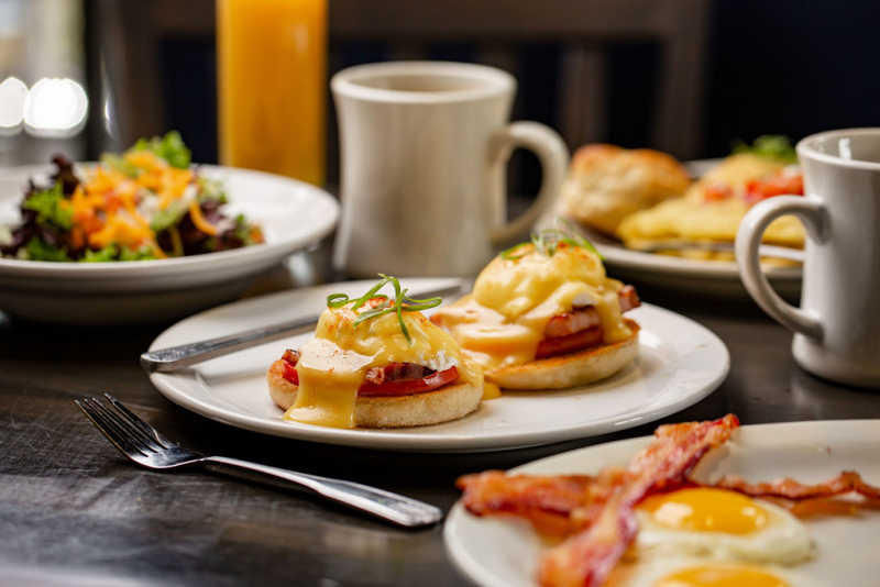 An order of eggs Benedict is accompanied by sunny side up eggs, crispy slices of bacon, and two mugs of freshly brewed coffee.