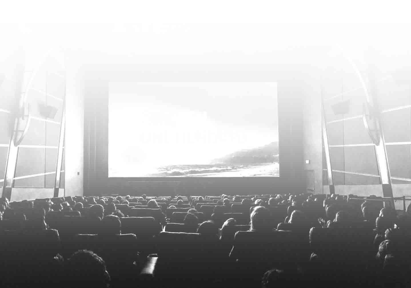 Auditorium full of people facing a movie screen