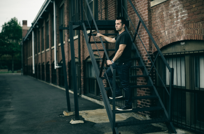 Chris Savage outside, standing on metal staircase looking out