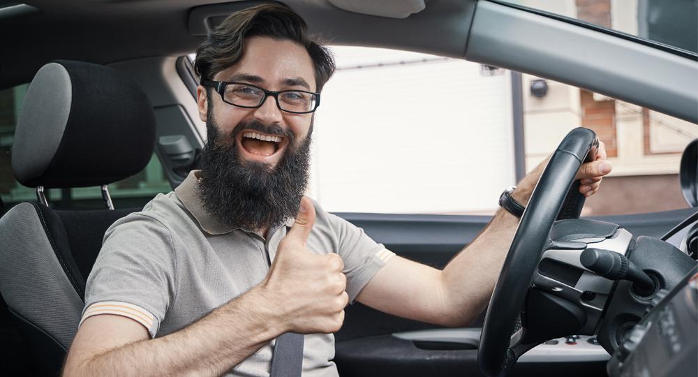 homme barbu leve pouce dans voiture