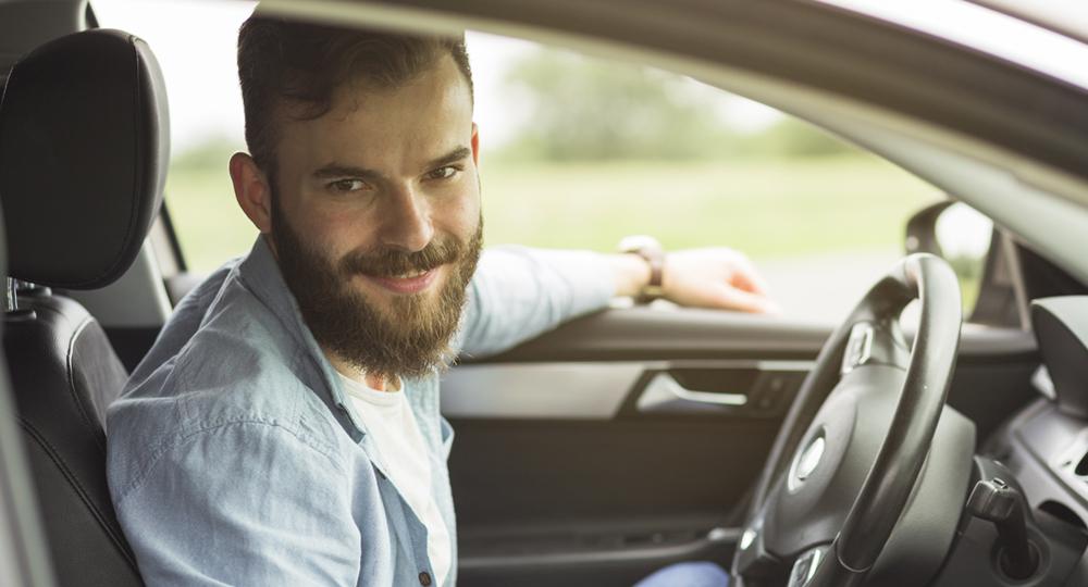 homme qui sourit au volant