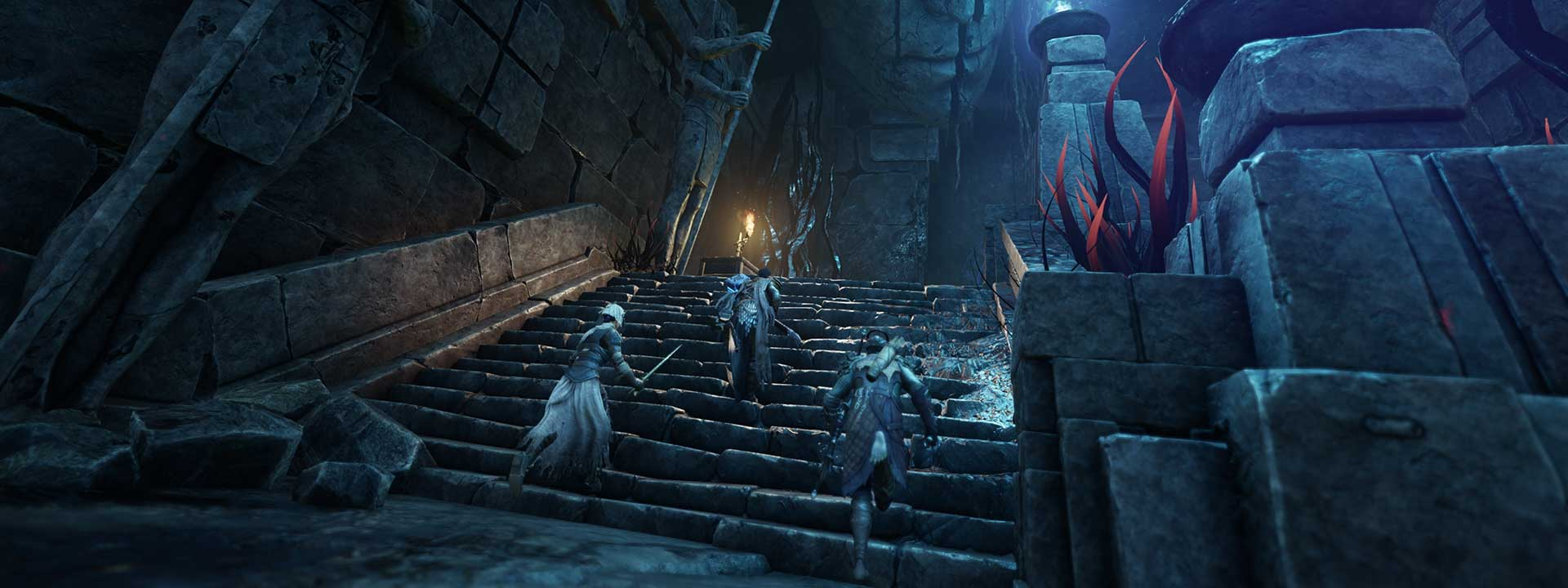 A group of adventurers with their weapons draw race up a flight of ancient stone stairs. The stairway is dimly lit with blue and orange flame sconces.