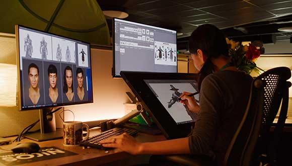 An artist uses a drawing tablet to work on character designs for New World